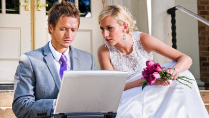 Newlyweds planning wedding on a computer